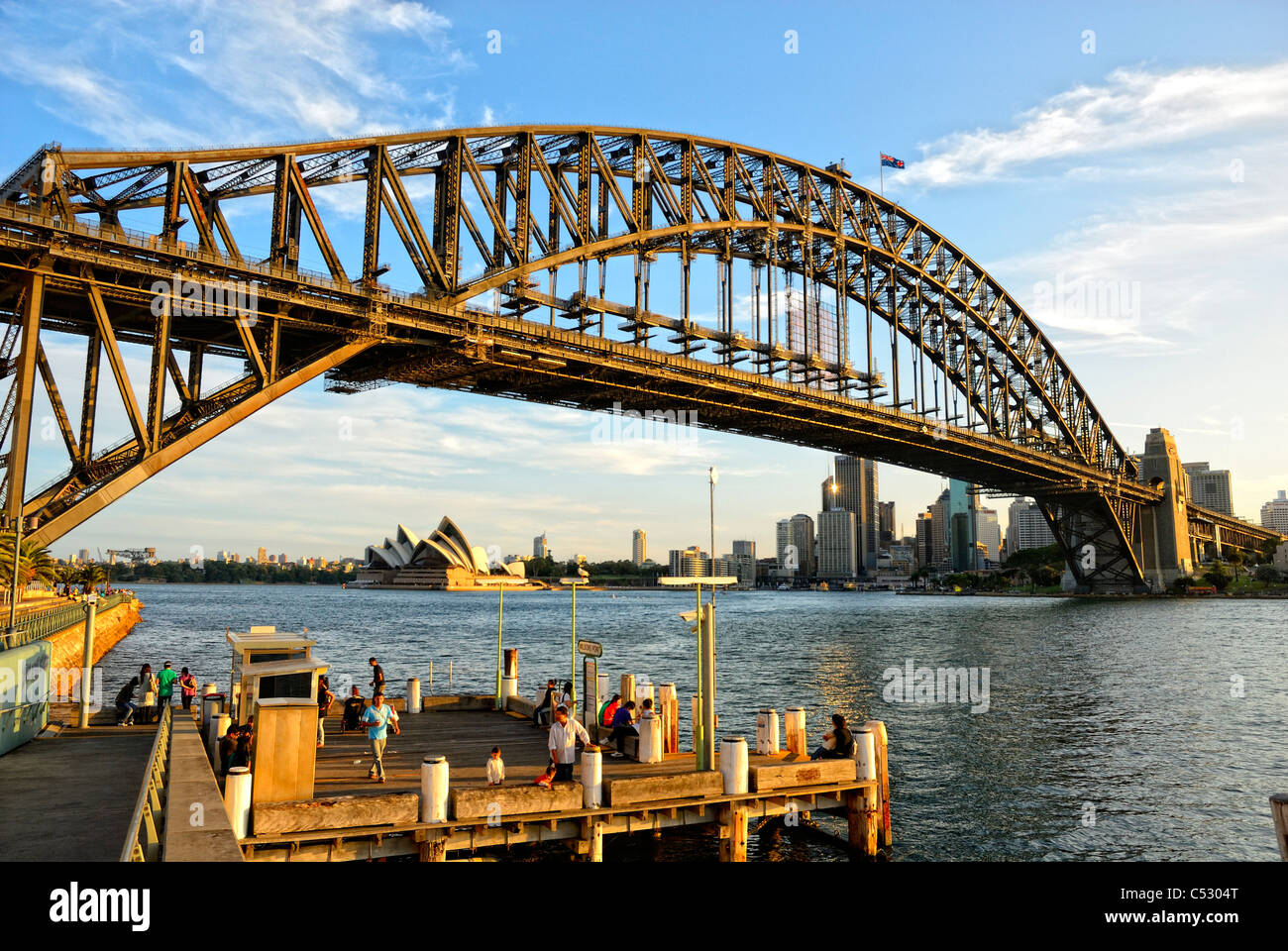 Sydney Harbour Bridge in the evening light, with the opera house in the background and Sydney Harbor below. Sydney - Stock Image