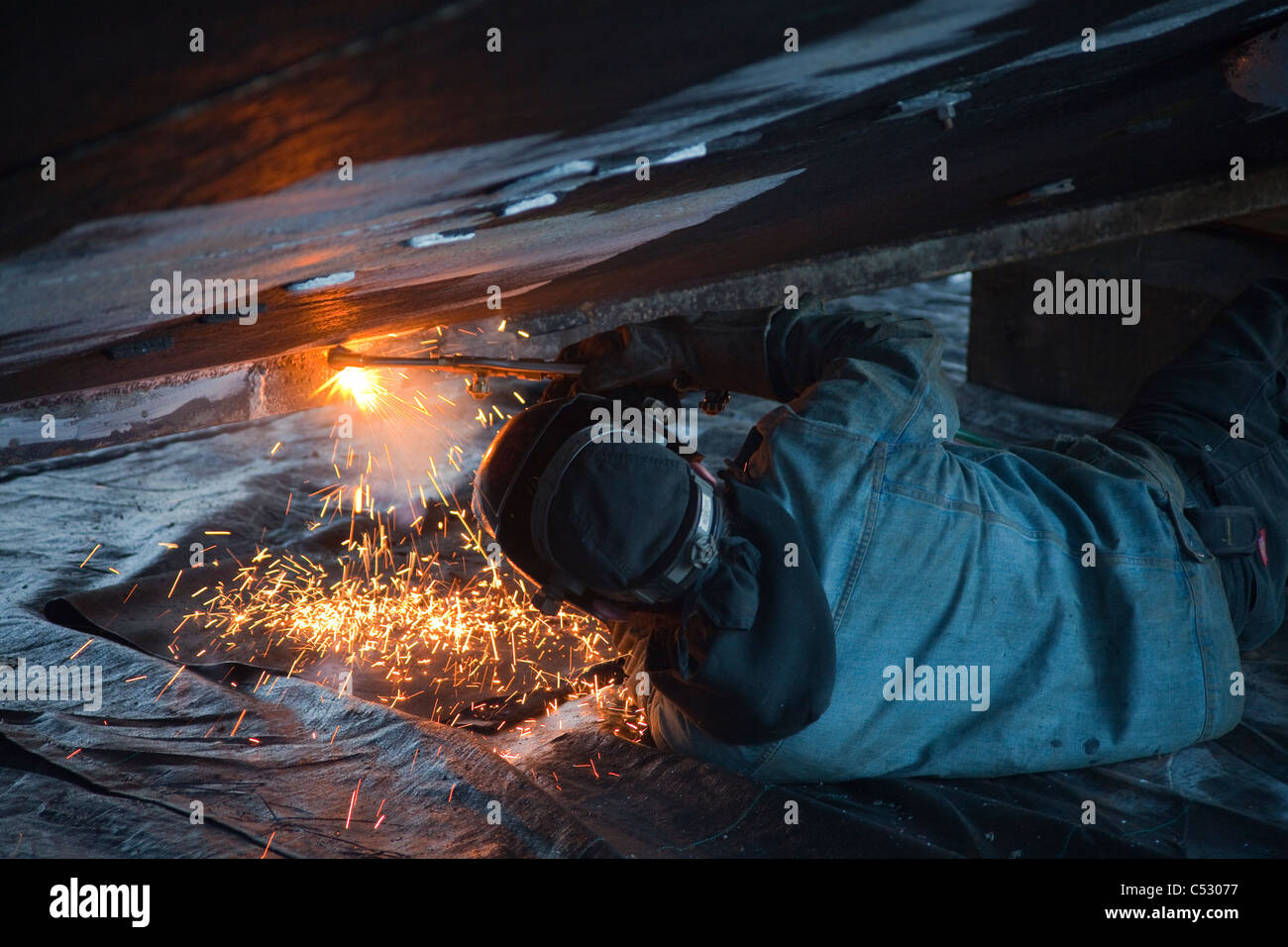 Worker cuts metal fittings off a boat hull, Kodiak Boatyard, Saint Herman Harbor, Kodiak, Near Island, Alaska Stock Photo