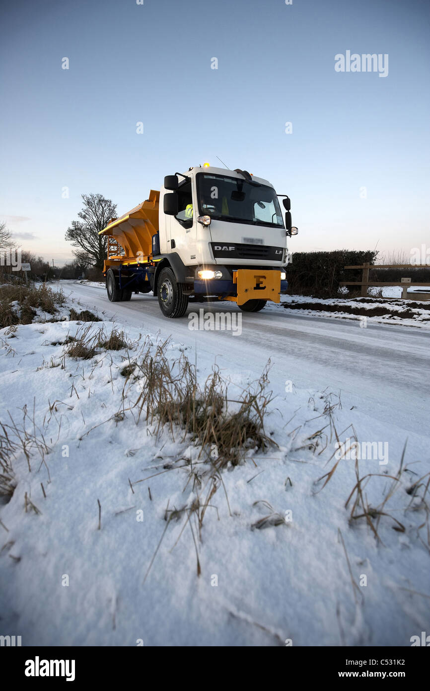 Gritter spreading grit over a snow covered lane, UK. - Stock Image