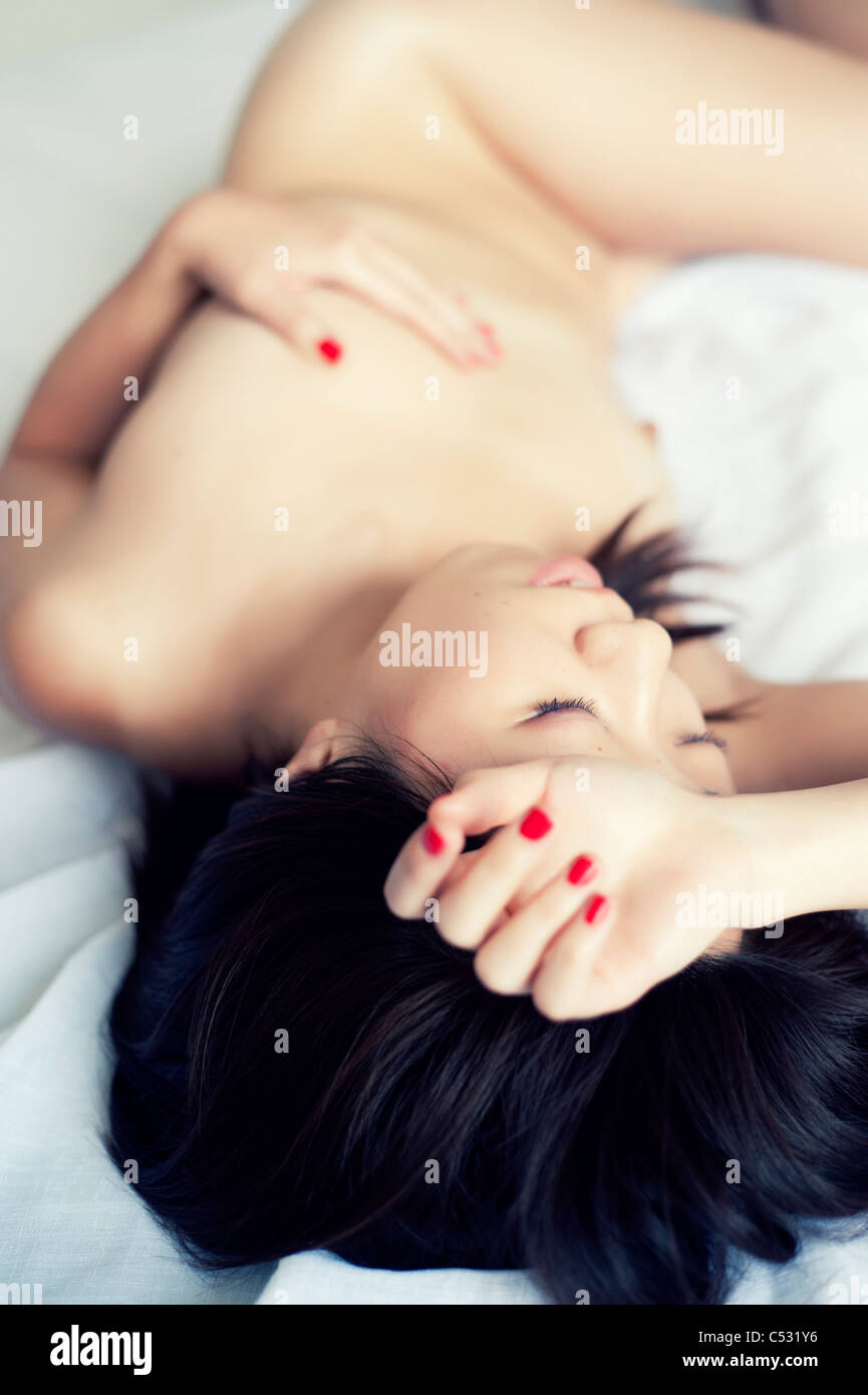 Young Japanese Woman Lying On A Bed Nake