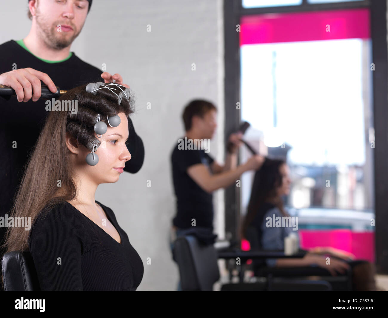 Young woman having her hair done by a hairstylist at a salon - Stock Image