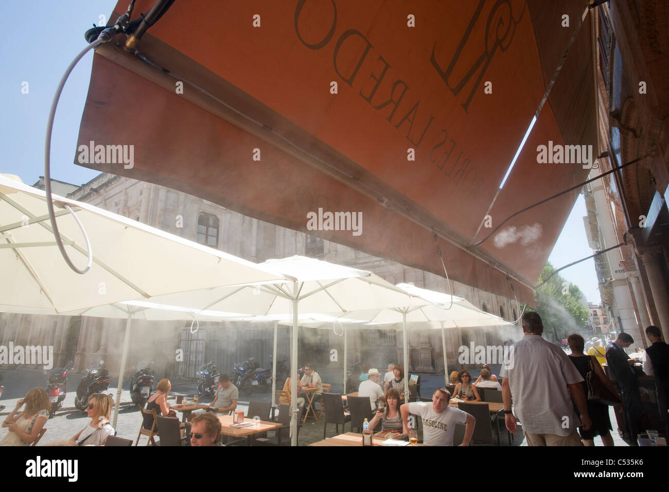 A cafe cooling customers down with a misting system during a heat wave in Seville, Spain. - Stock Image