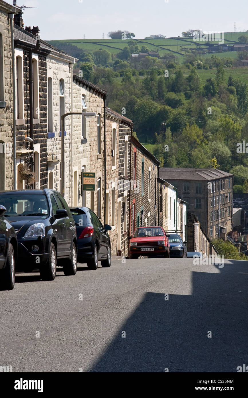 Terraced housing with Mill and open country beyond, Colne, Lancashire, England, UK - Stock Image