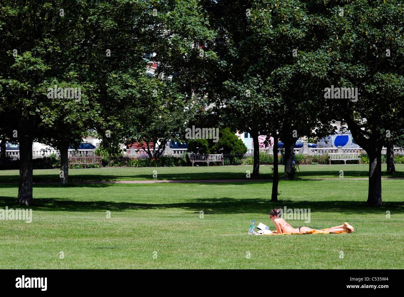 Mature woman sunbathing in public park