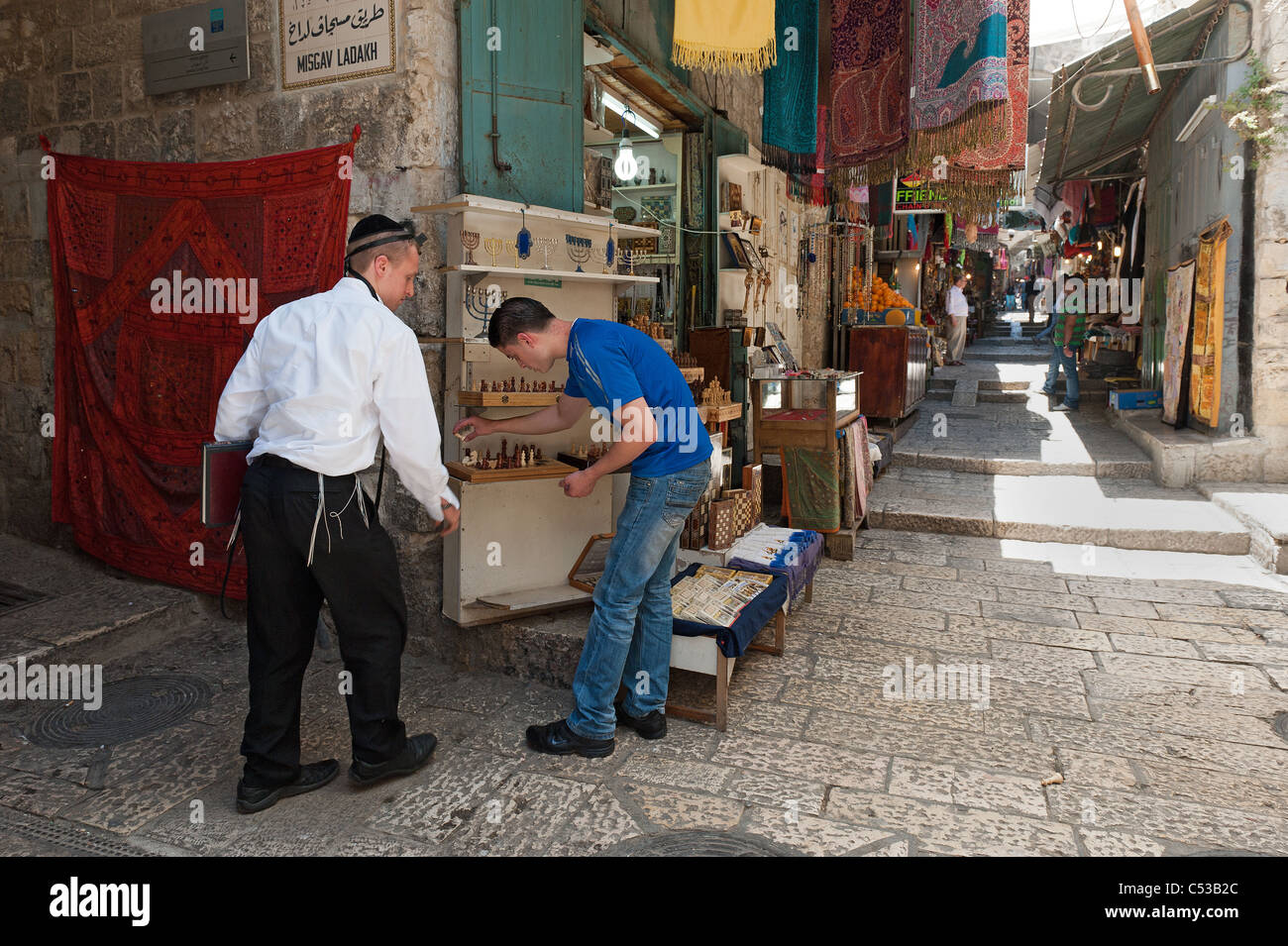 A religious Jew helps an Arab seller arrange his goods - Stock Image