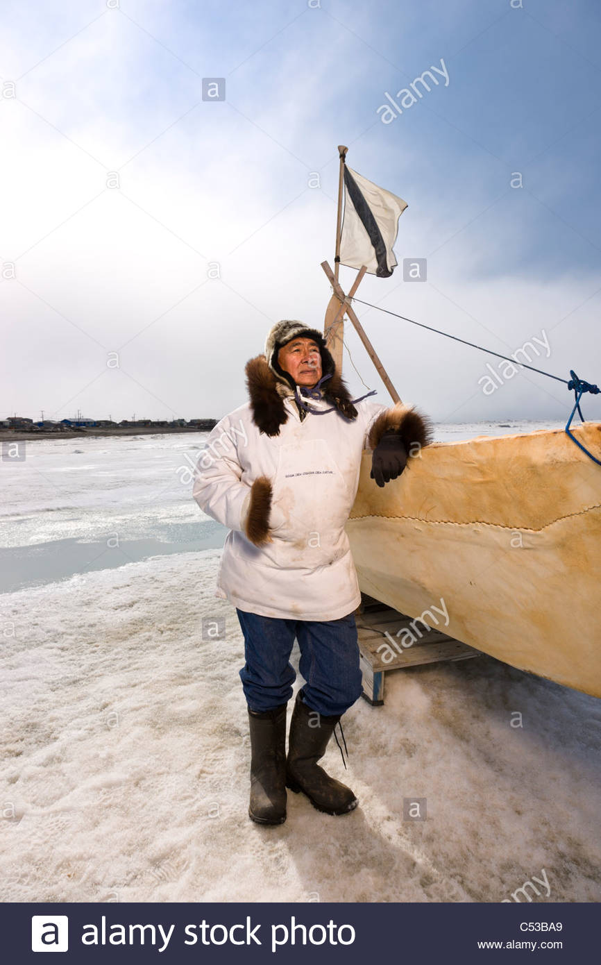 Male Inupiaq Eskimo hunter stands beside an Umiaq wearing a traditional Eskimo parka  and seal skin hat, Chukchi - Stock Image