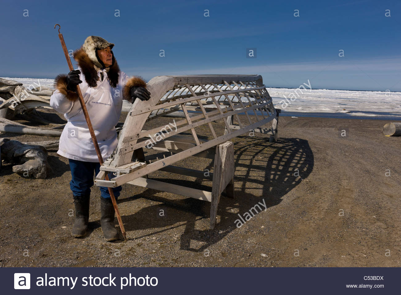 Male Inupiaq Eskimo hunter wearing his Eskimo parka , standing in front of a Bowhead whale bone arch and Umiaqs, - Stock Image