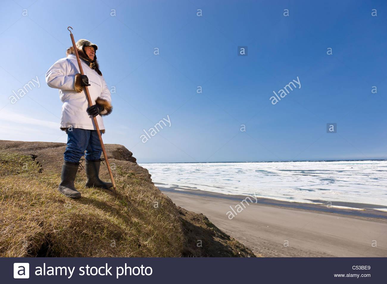 Inupiaq Eskimo holding a walking stick at Old Utkeagvik original town site overlooking the Chukchi Sea, Barrow, - Stock Image