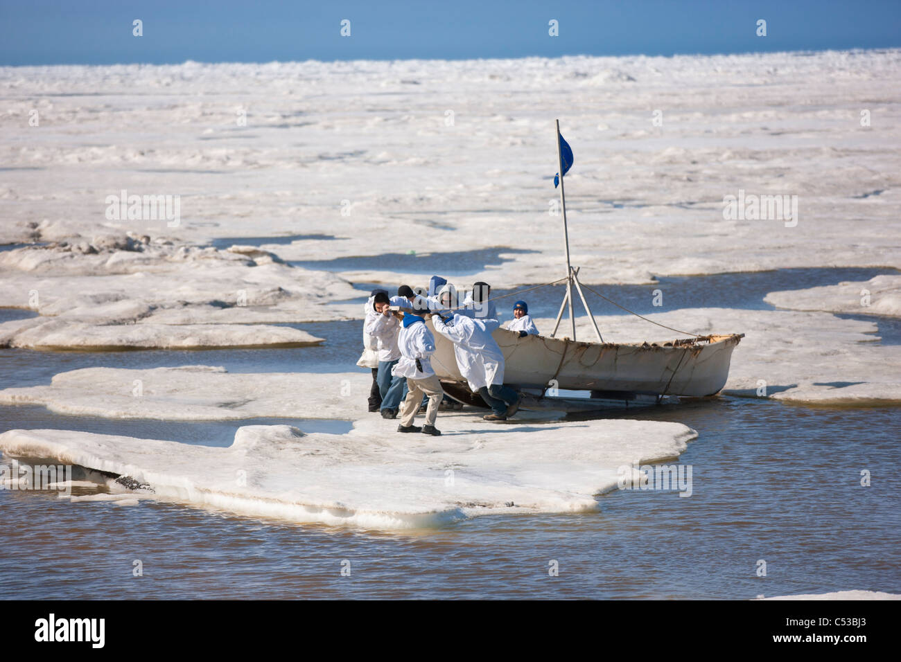Whaling crew pushes their Umiaq off the Chuchki Sea ice at the end of the spring whaling season in Barrow, Arctic - Stock Image