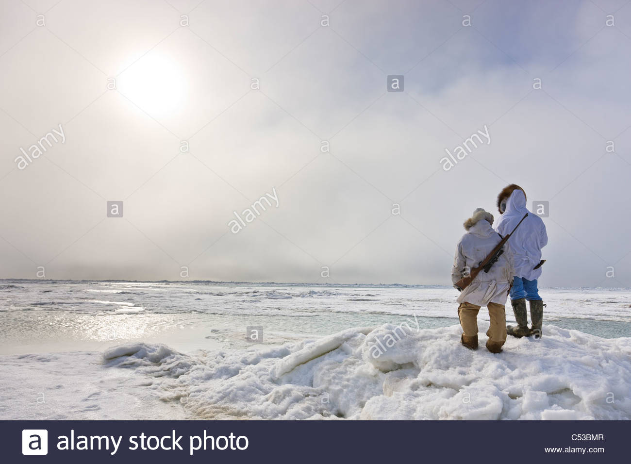 Inupiaq Eskimo hunters in parkas  carry a rifle and walking stick while looking out over the Chukchi Sea, Barrow, - Stock Image