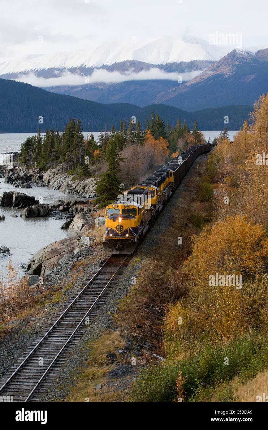 Alaska Railroad hauls coal past Rocky Cove at Bird Point along Turnagain Arm, Southcentral Alaska, Autumn - Stock Image