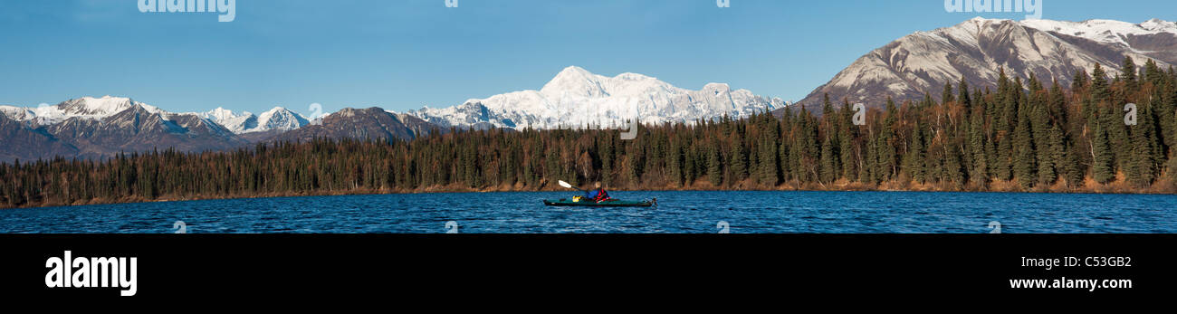 Woman kayaking in Byers Lake with scenic view of Mt. McKinley on a clear sunny day, Denali State Park, Alaska - Stock Image