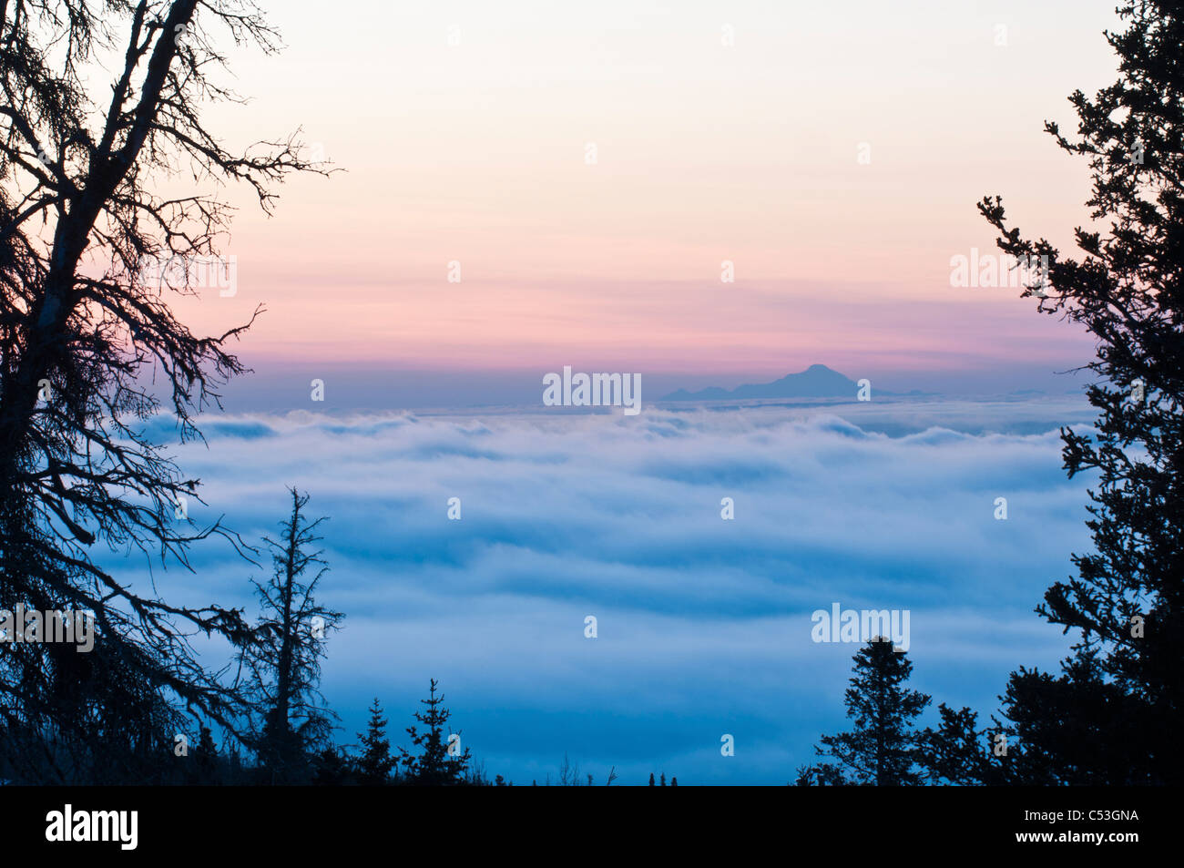 Scenic view of a low layer of fog over Anchorage with Mt. Redout visible above the fog  in the background, Alaska, - Stock Image