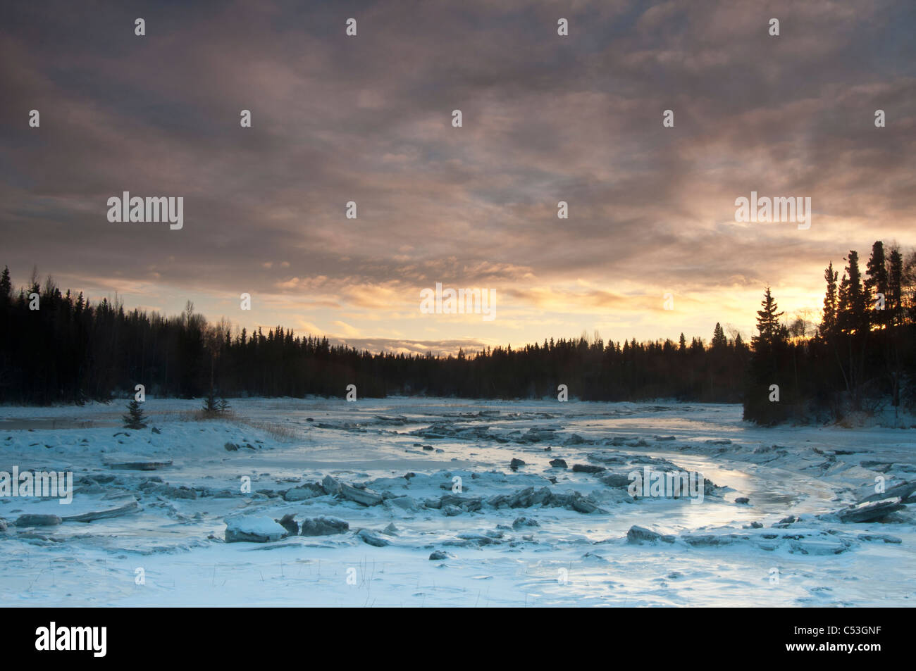 An ice-covered Fish Creek reflects the afternoon sky near the Tony Knowles Coastal Trail and Westchester Lagoon, Stock Photo