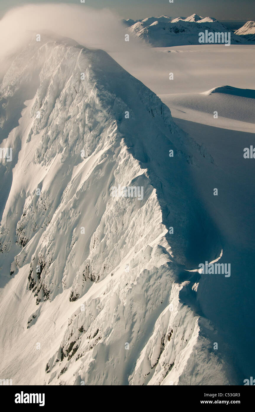 Strong winds sweep snows over a peak on the Harding Ice Field in Kenai Fjords National Park, Southcentral Alaska, - Stock Image