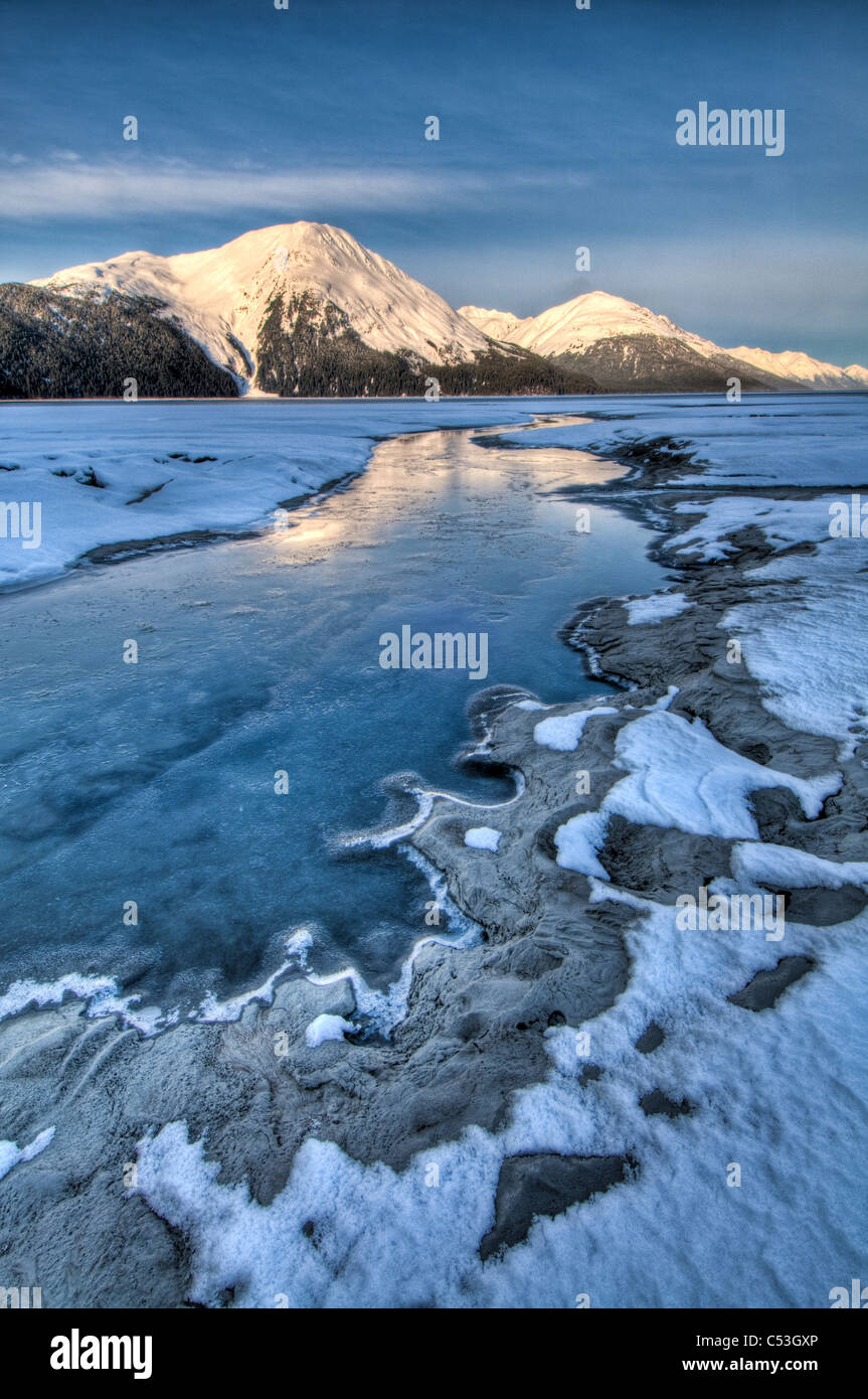 Morning light on the Kenai Mountains reflects on the waters and ice of Turnagain Arm, Southcentral Alaska, Winter. Stock Photo