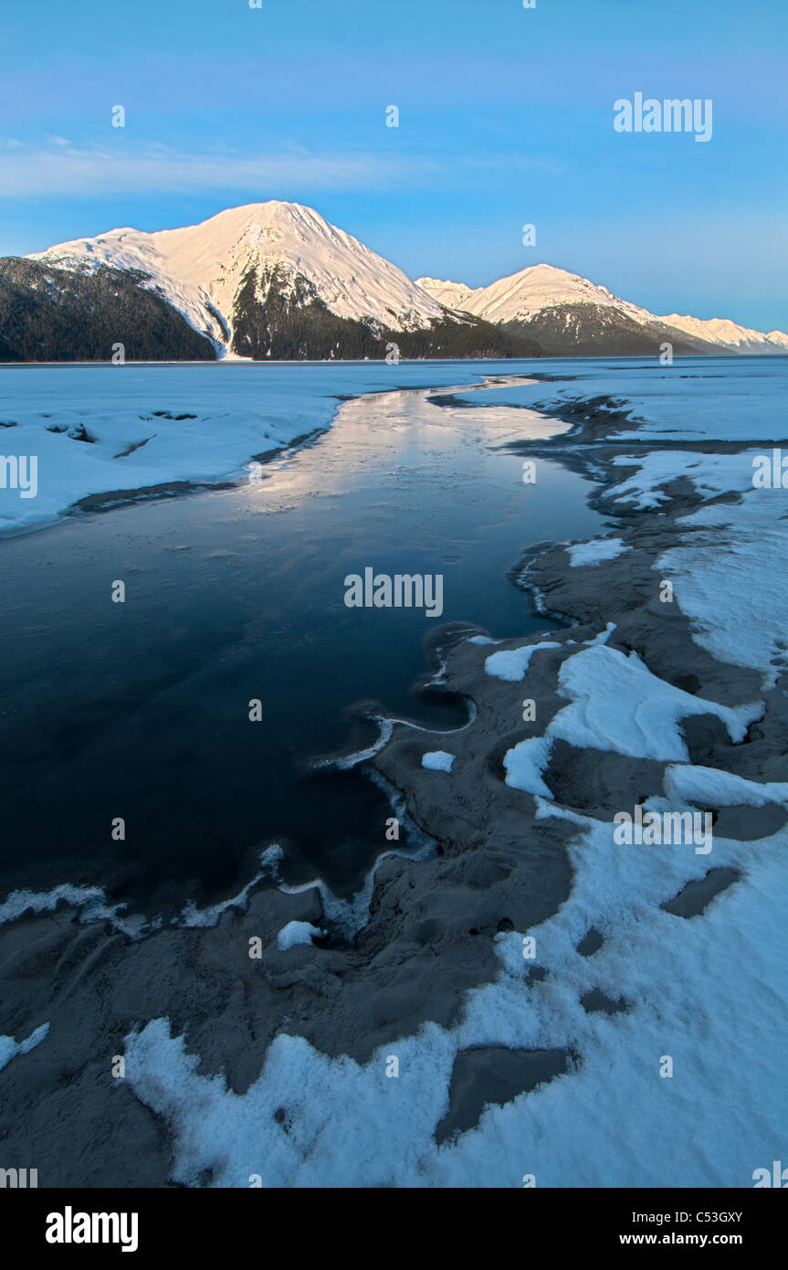 Morning light on the Kenai Mountains reflects on the waters and ice of Turnagain Arm, Southcentral Alaska, Winter. - Stock Image
