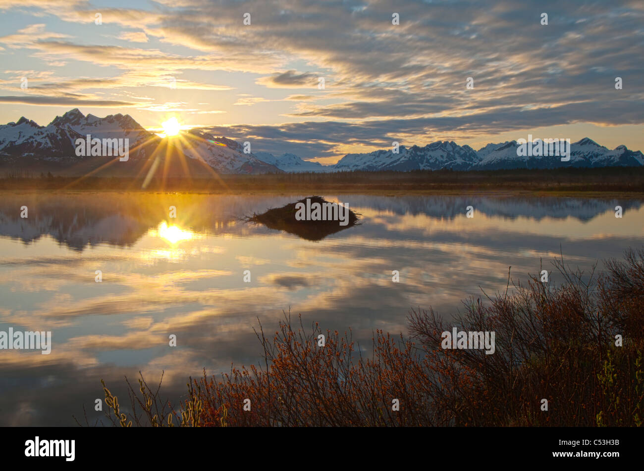 Sun rises over the Chugach Mountains with a pond and beaver lodge in the foreground, Chugach National Forest, Alaska - Stock Image