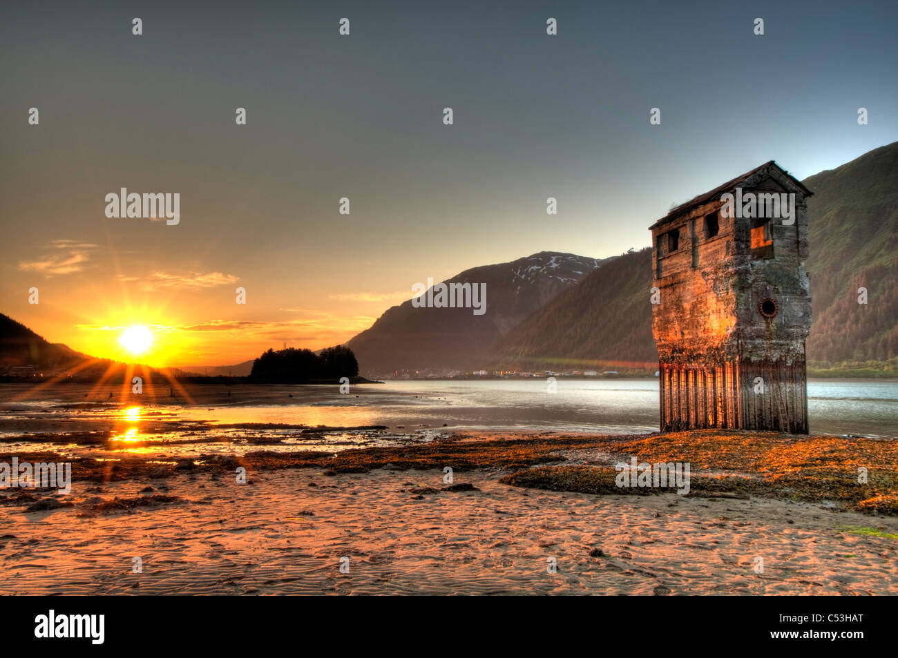 View of an old placer mining operation on the shore of Douglas Island at sunset, across from Juneau, Alaska, HDR. Stock Photo
