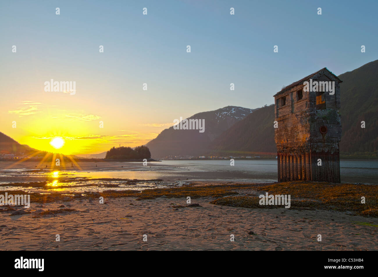 View of an old placer mining operation on the shore of Douglas Island at sunset, across from Juneau, Alaska, HDR. - Stock Image