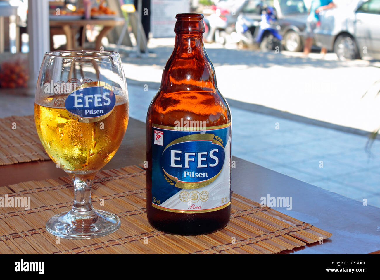 Efes Pilsen Beer Bottle and Glass on restaurant Table in Side, Turkey Stock Photo