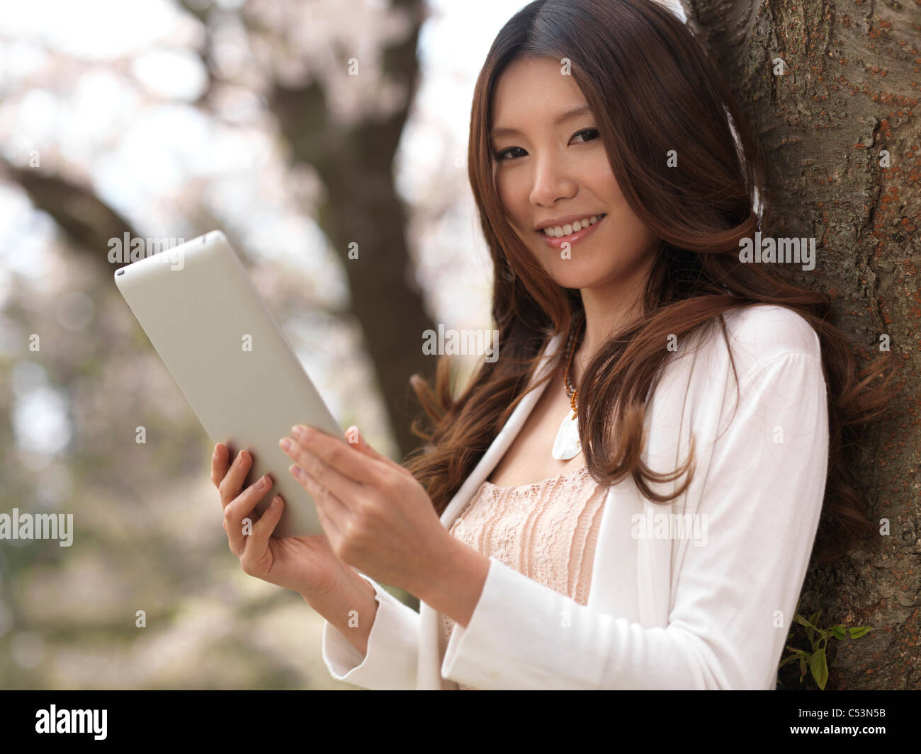 Young smiling Asian woman with a tablet computer in a park under a cherry tree - Stock Image
