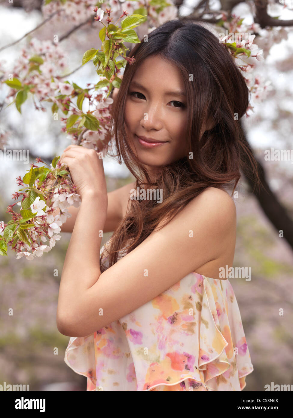 Portrait of a beautiful young smiling Asian woman standing at a blooming cherry tree in a park Stock Photo