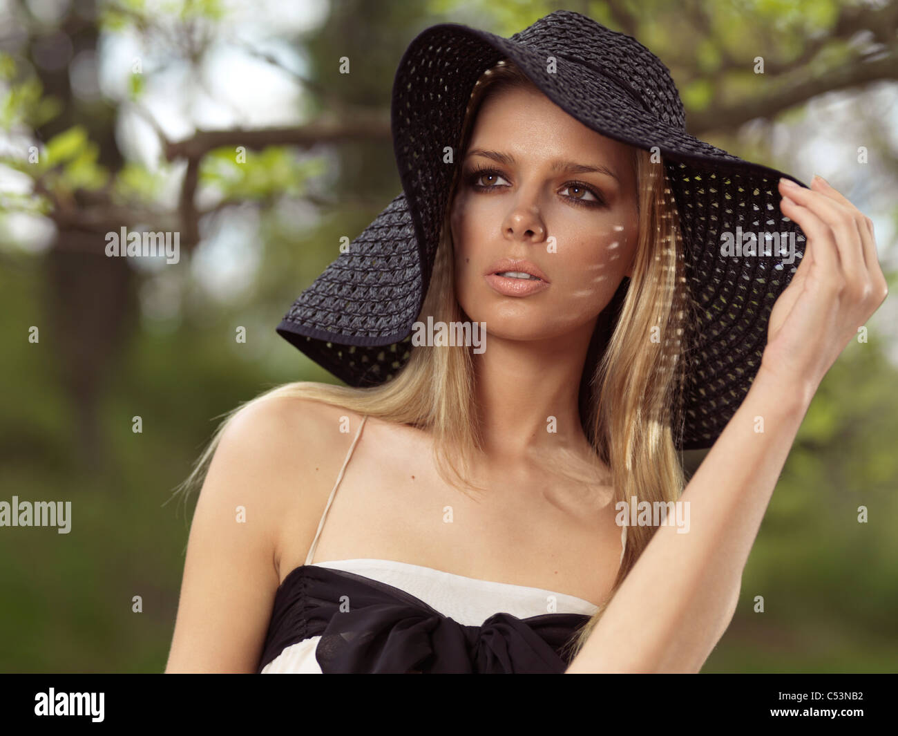 8aae72004ce Portrait of a beautiful young woman wearing a sun hat - Stock Image
