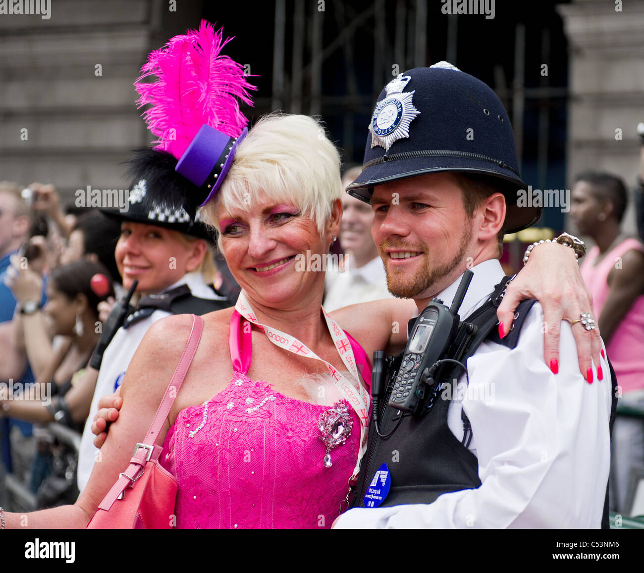 A Gay Pride participant embracing a London police officer. - Stock Image