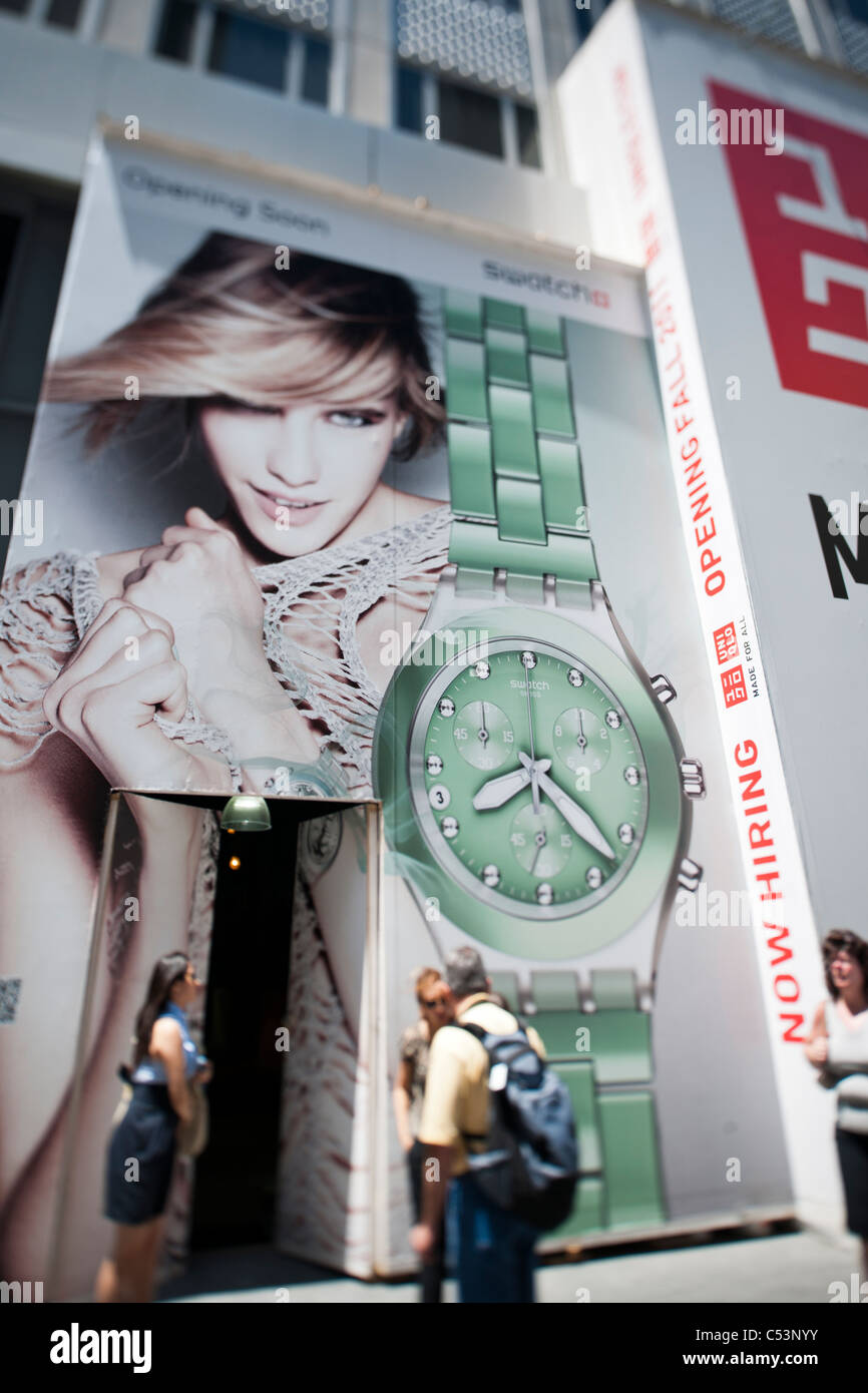 A billboard on a construction shed on Fifth Avenue in New York announces the eminent arrival of a Swatch store - Stock Image