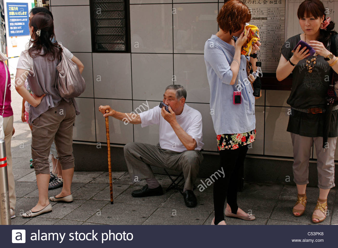 Hot summer day in Tokyo; an elderly man uses a portable stool to rest at the Sensoji temple, Asakusa, Tokyo, Japan - Stock Image