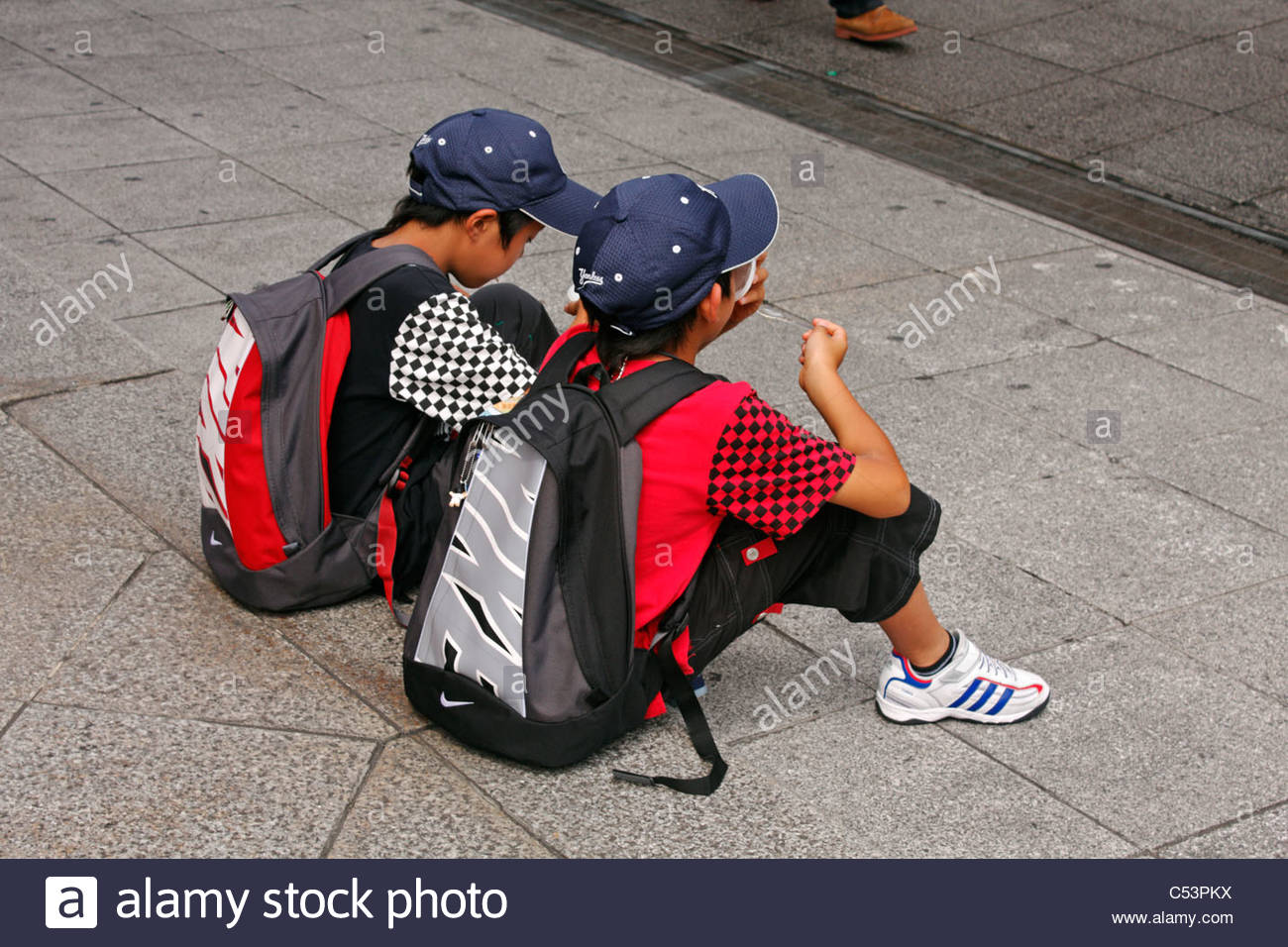 Two young boys in matching outfits, eating ice-cream, Asakusa, Tokyo, Japan - Stock Image