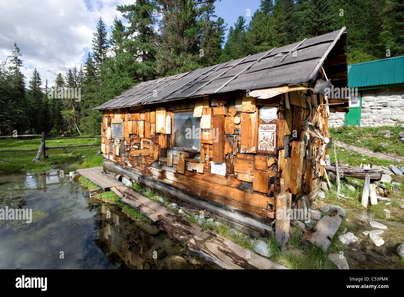 Wood hut in taiga with national symbols, images and mineral bath inside. Mineral springs Sayan Mountains. Siberia. - Stock Image