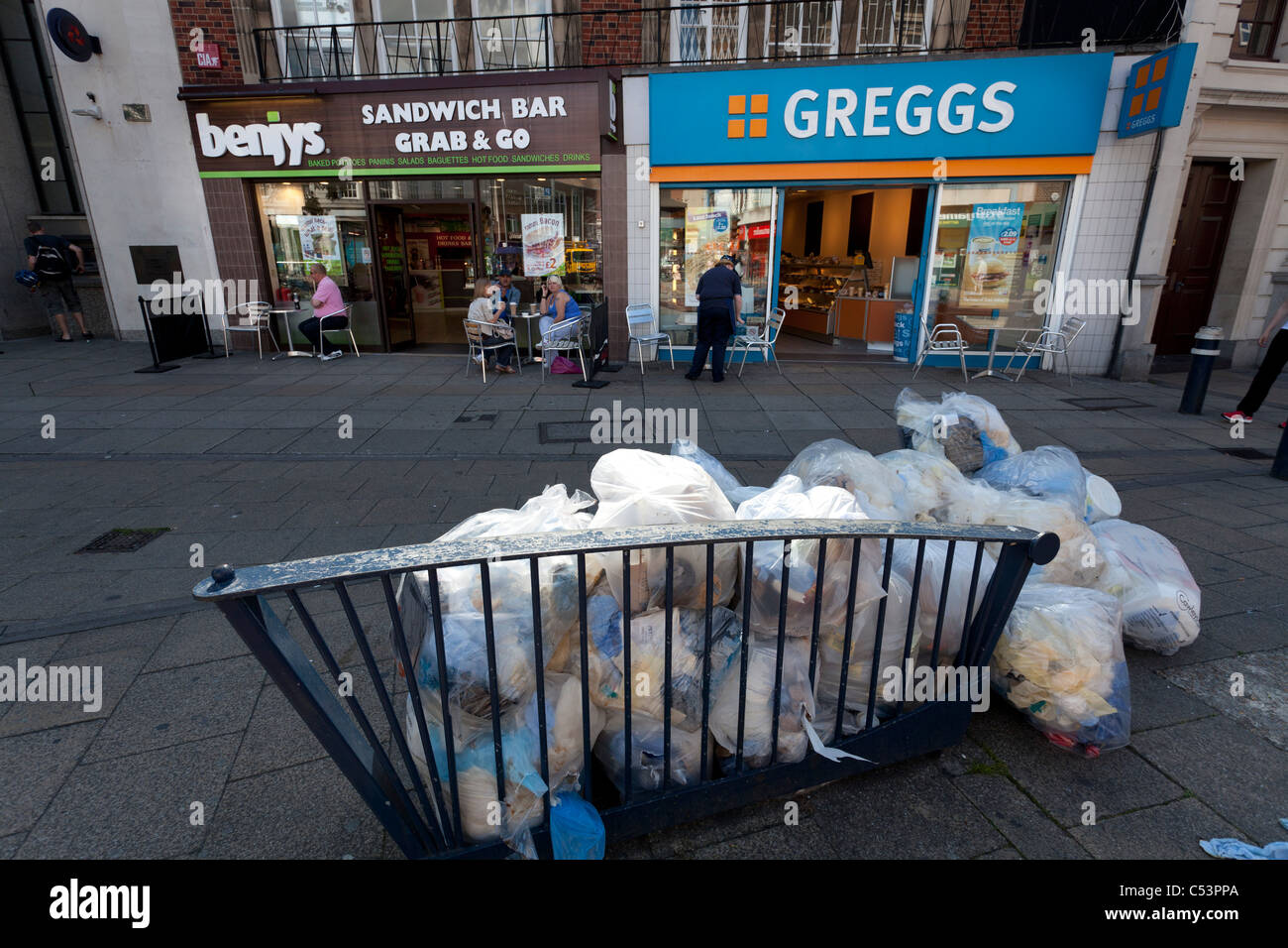 rubbish bags piles up outside fast food shops - Greggs and Benjys - Stock Image
