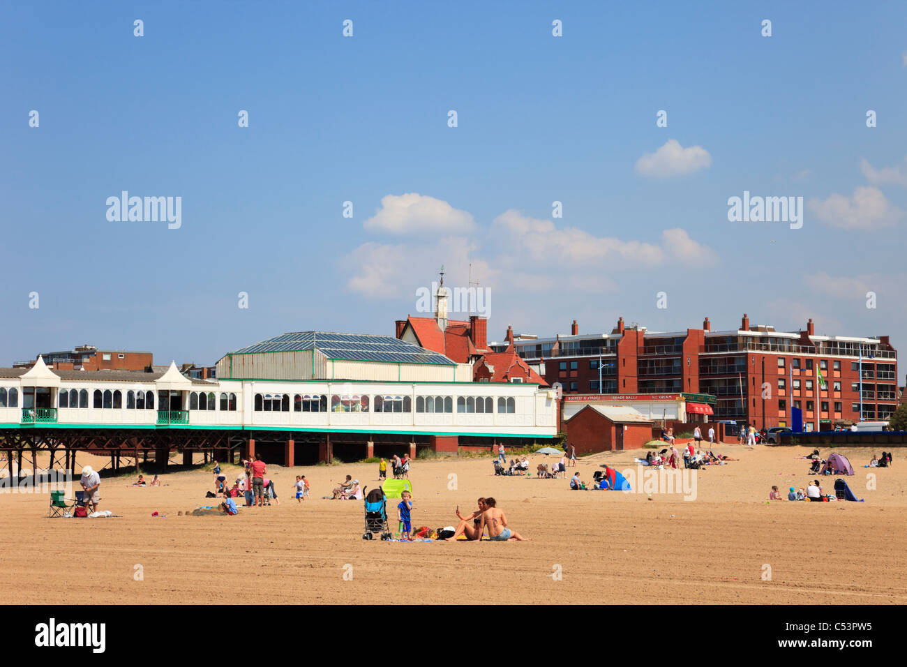 Lytham St Annes, Lancashire, England, UK. Holidaymakers on sandy beach by the pier in seaside resort - Stock Image