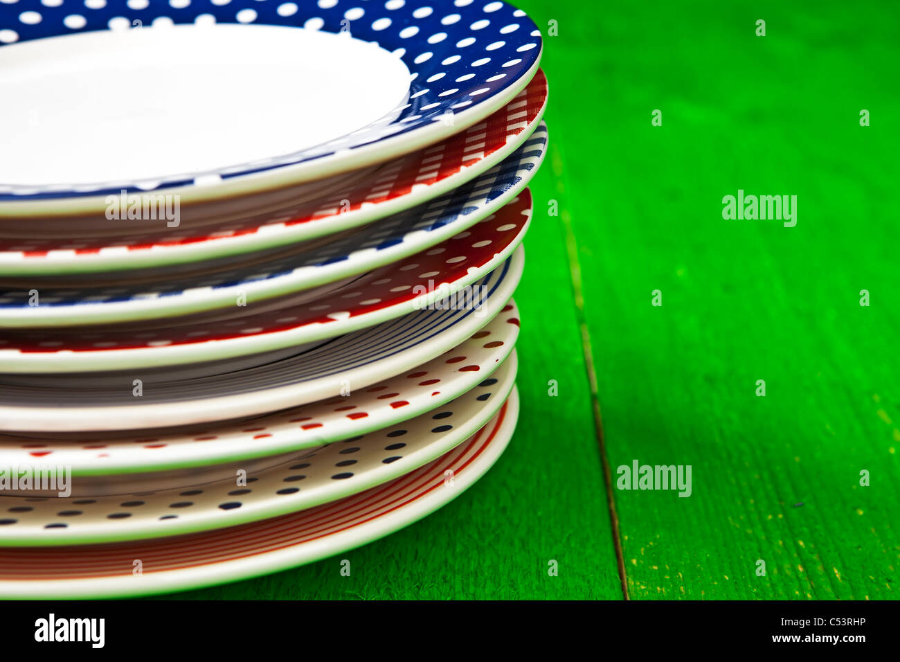 rustic and colorful plates on a green wooden table - Stock Image