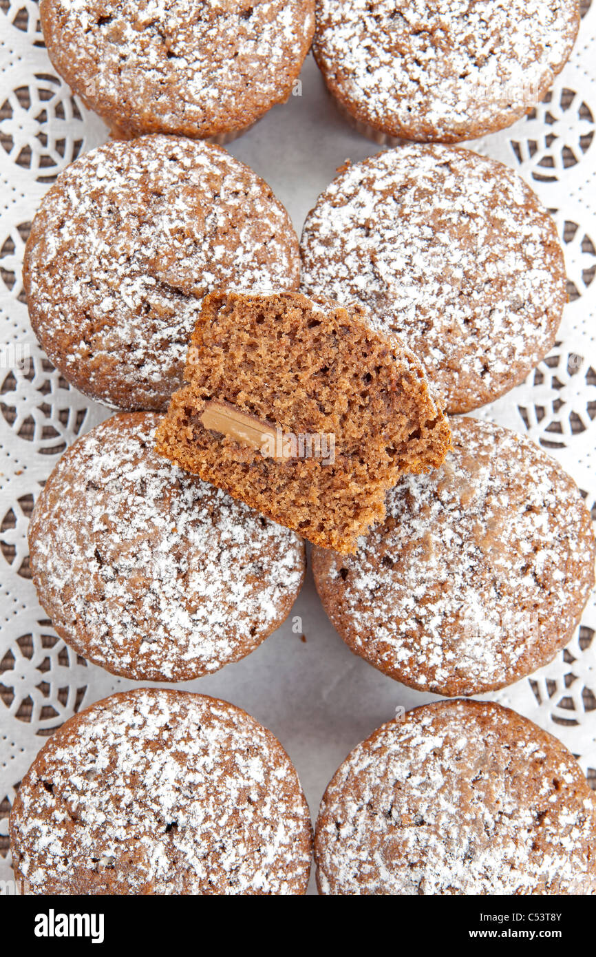 freshly baked chocolate muffins sprinkled with powdered sugar - Stock Image