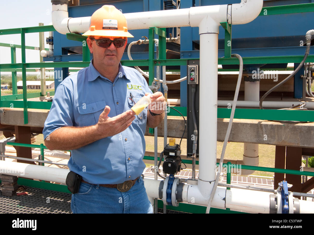 White male worker holds up a sample of processed Uranium at an Uranium processing plant in Texas Stock Photo