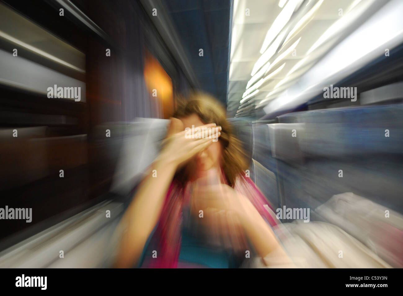 Zoom motion blur effect on girl hiding her face. Suggests shyness, embarrassment, shame paranoia concepts - Stock Image