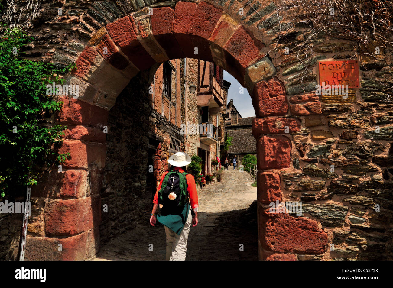 France, St. James Way: Woman passing the medieval village gate 'Porte du Barry' in Conques - Stock Image