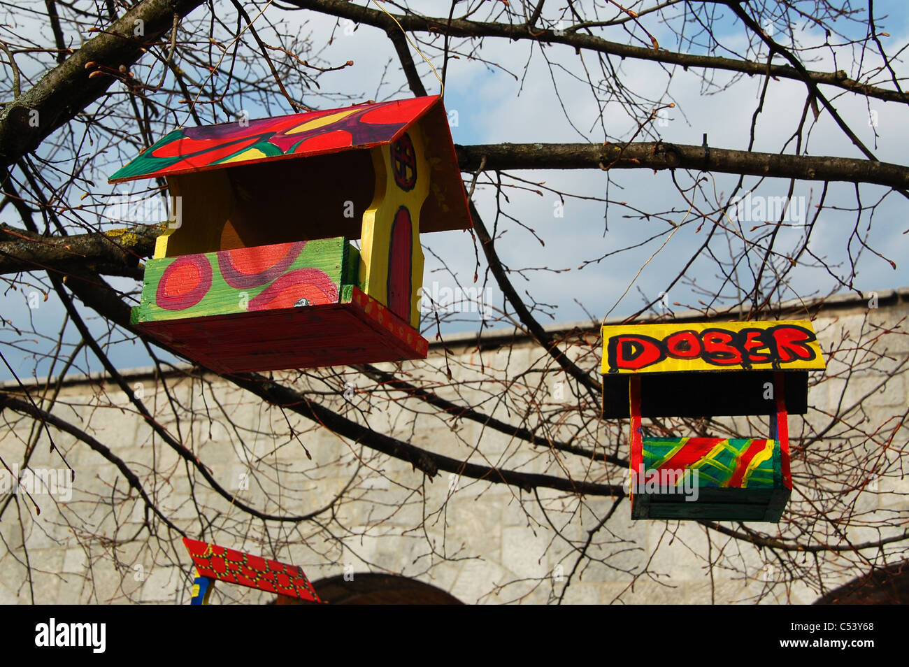 Two colourful / colorful wooden birdhouses hang from a leafless tree. - Stock Image