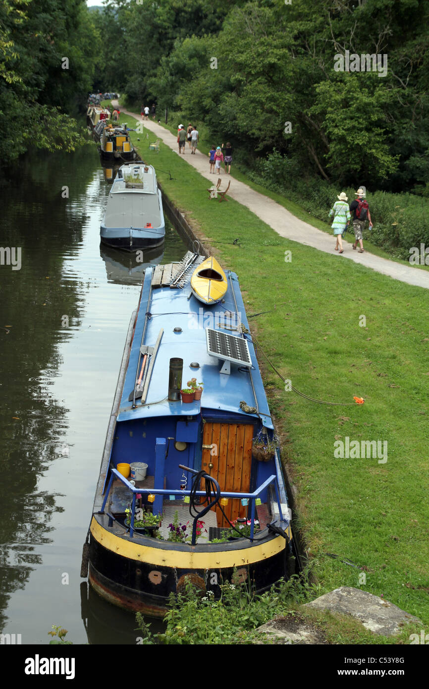 PEOPLE WALK AND CYCLE PAST BARGES ALONG THE KENNET AND AVON CANAL IN WILTSHIRE, ENGLAND, UK Stock Photo