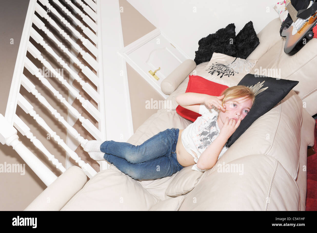 young girl laid on sofa, relaxing - Stock Image