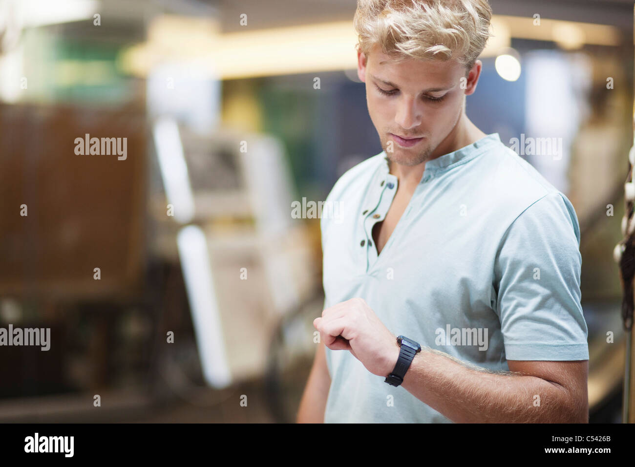 Young man checking the time in a clothing store - Stock Image