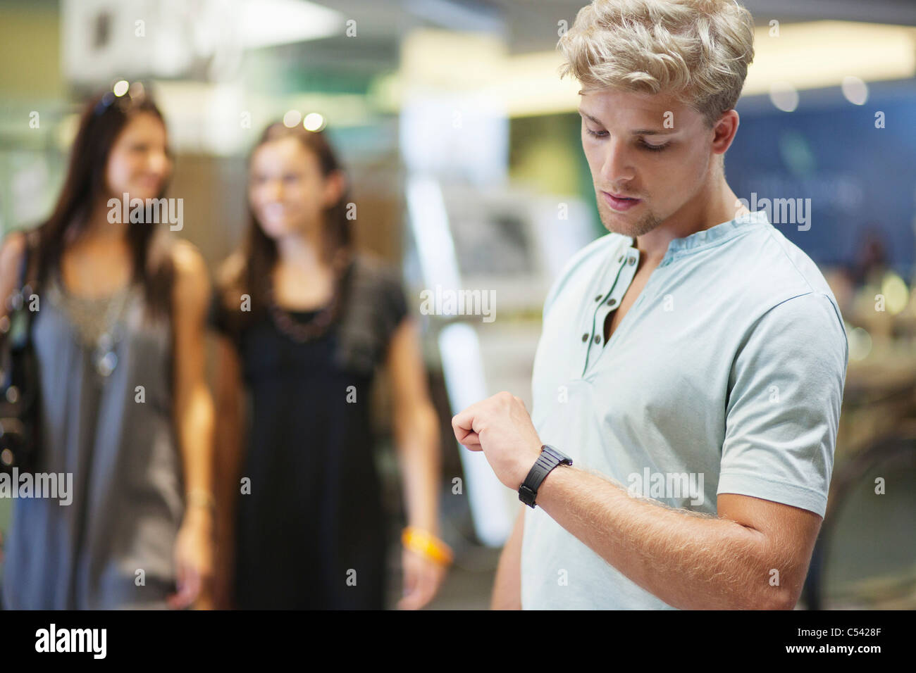 Young man checking the time with two women in the background at a clothing store - Stock Image