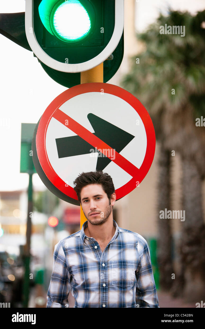 Man with 'No Entry' sign and traffic light in the background - Stock Image