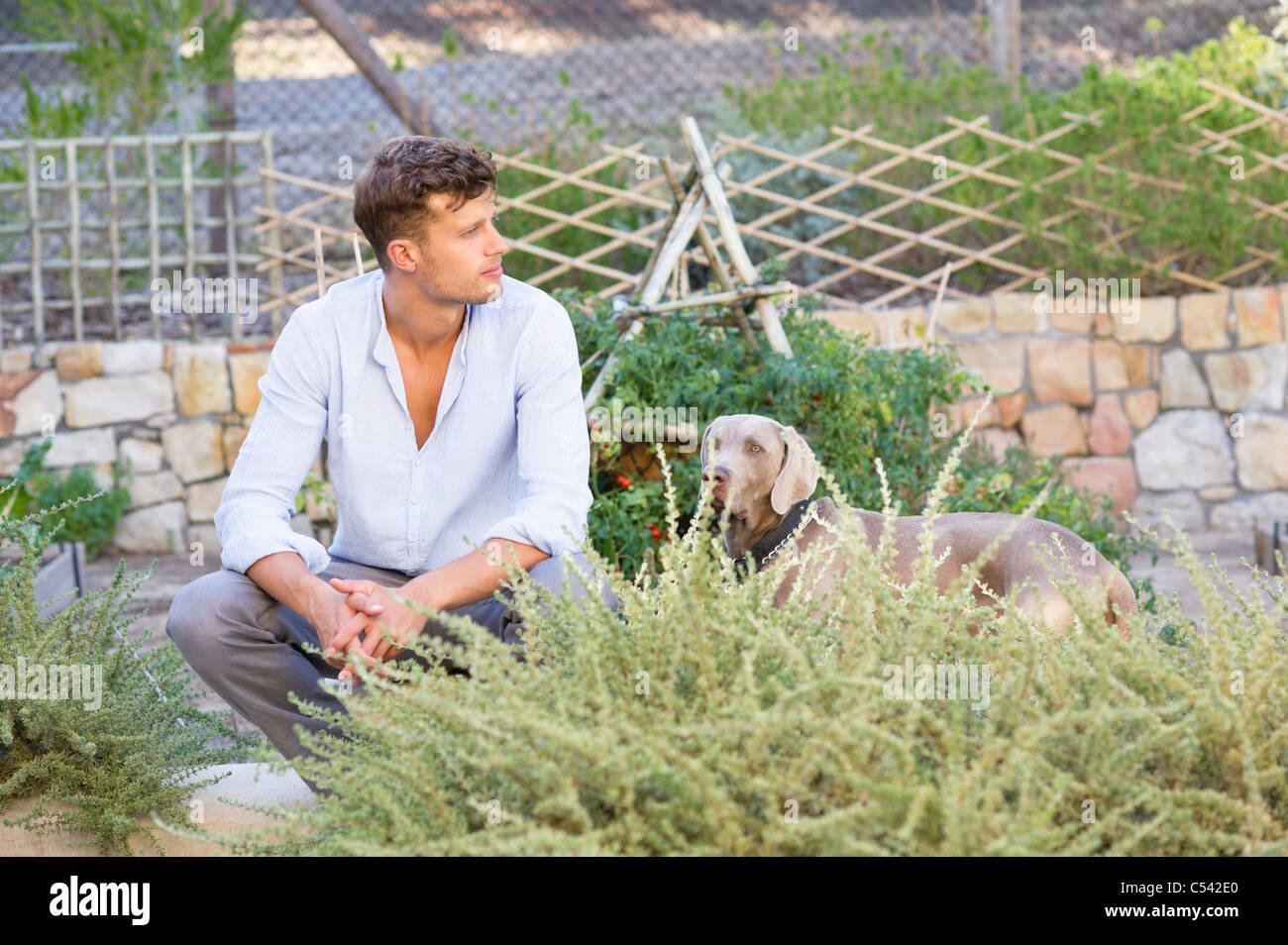 Contemplative man with a dog in garden Stock Photo