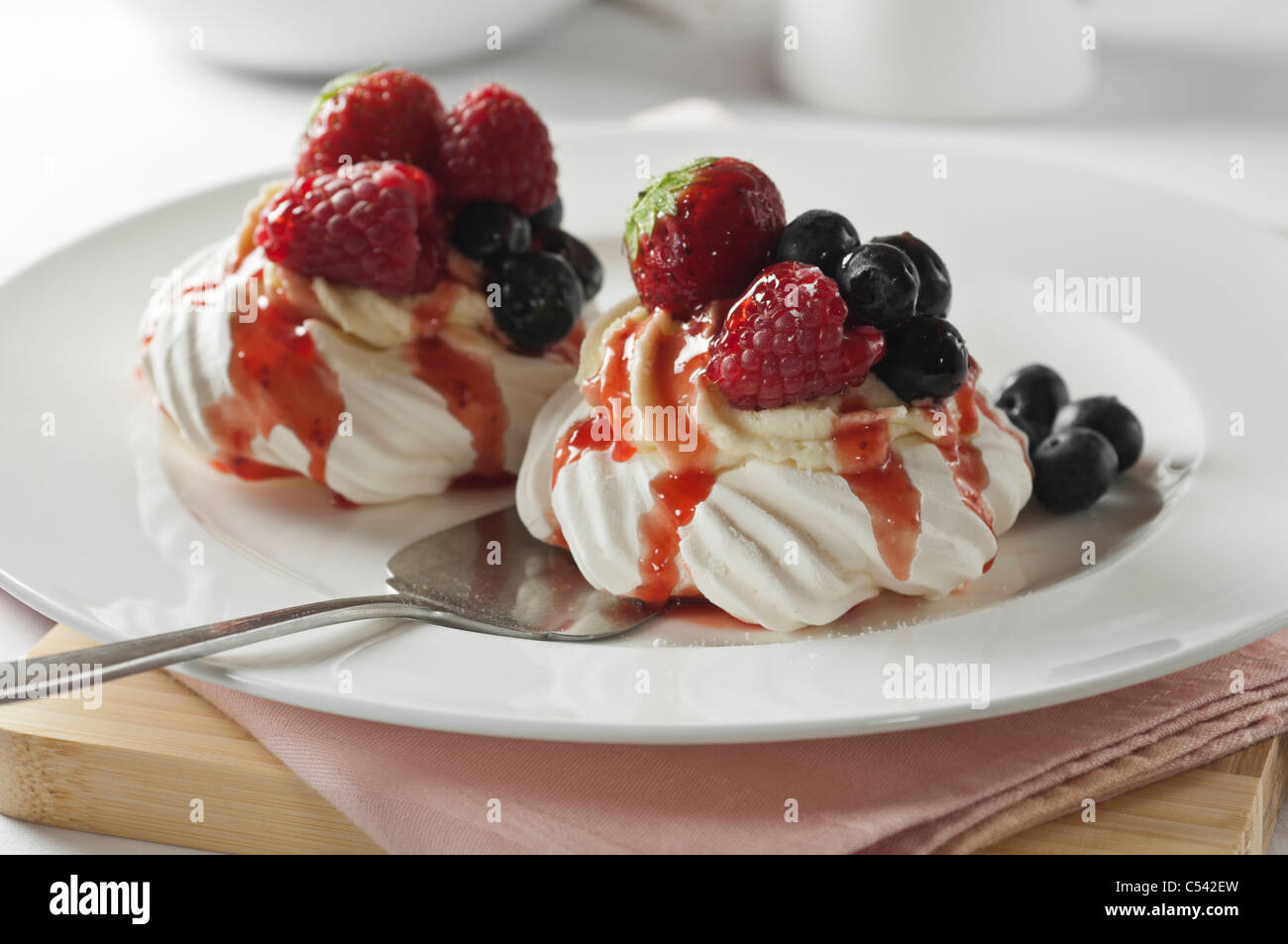 Meringue nests with fruit and cream - Stock Image