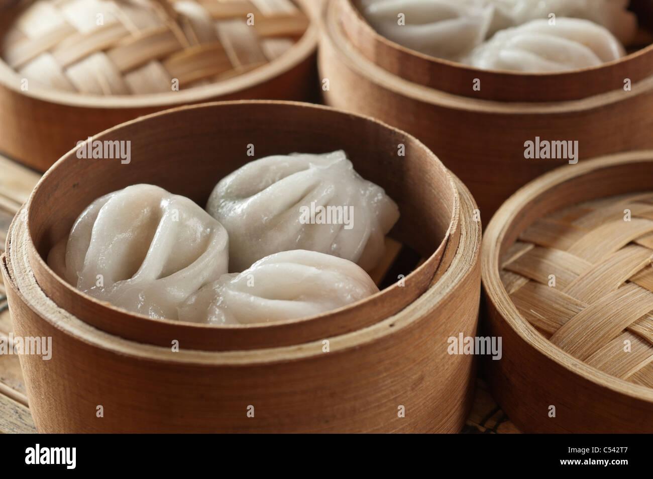 Dim sum. Steamed dumplings in steamer baskets - Stock Image