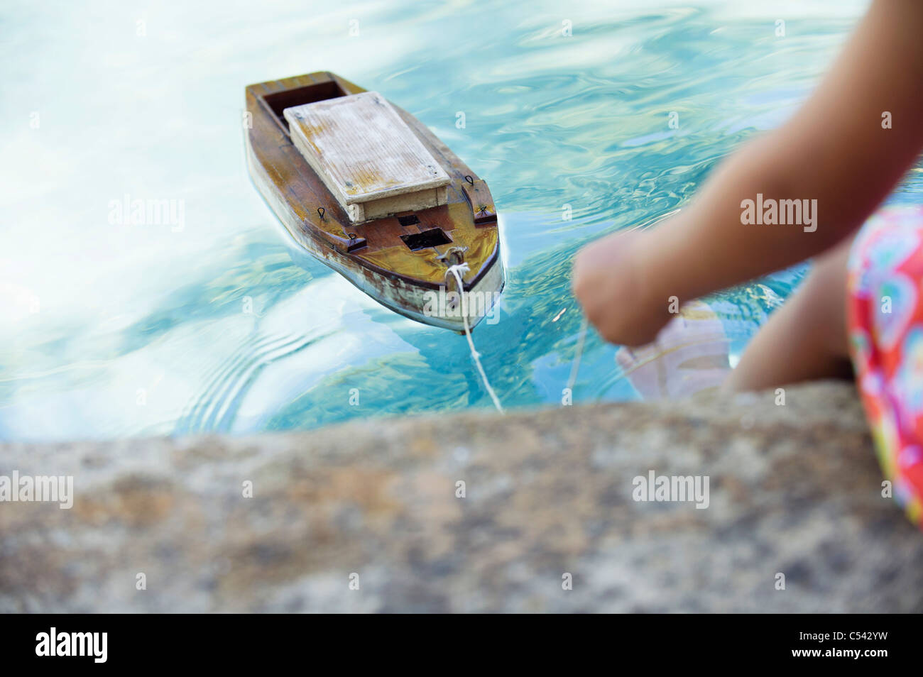 Low section view of a girl sitting at edge of swimming pool with toy boat in water - Stock Image
